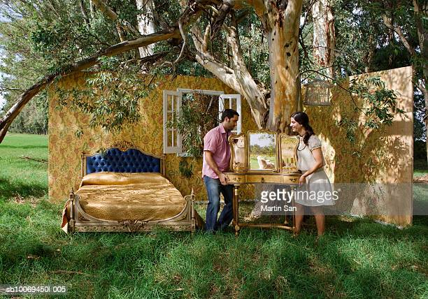 Couple moving mirror in bedroom beneath tree, side view