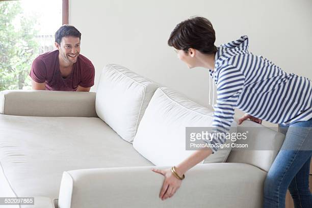 Couple moving sofa together