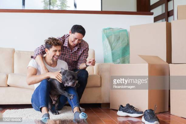 lgbt couple moving to their new home - home ownership stock pictures, royalty-free photos & images