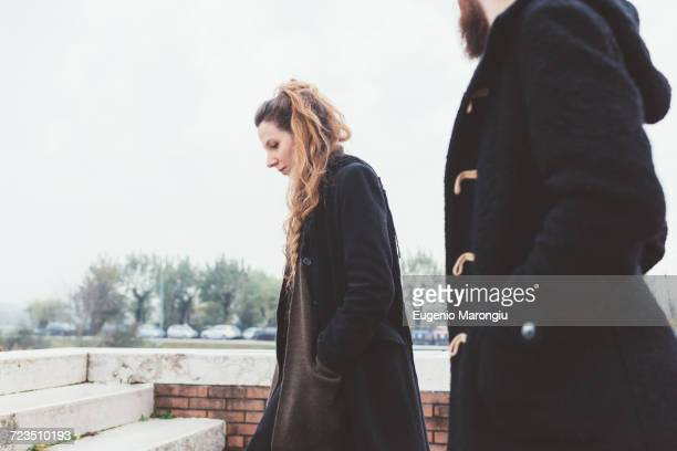 couple moving up stairway - ダッフルコート ストックフォトと画像