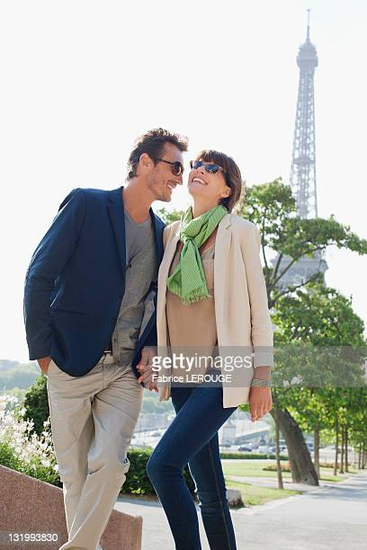 Couple moving up steps with the Eiffel Tower in the background, Paris, Ile-de-France, France