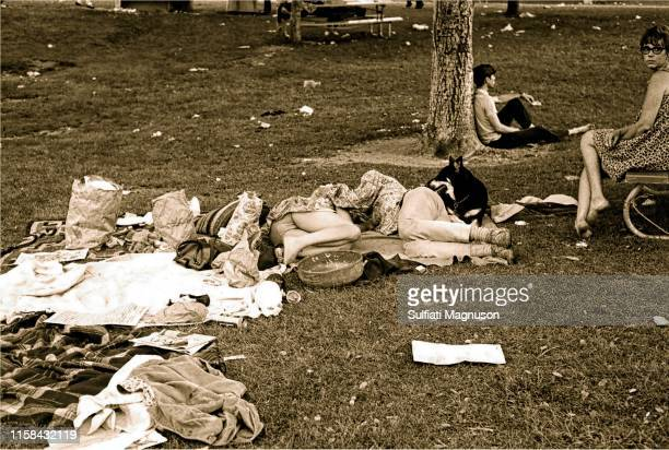 Couple napping, man leaning against a tree and a woman on a bench amid a trash-strewn picnic at the 1st Elysian Park Love-In on March 26, 1967 in Los...