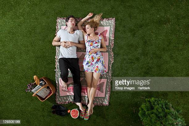 A couple napping on a blanket in a park, overhead view