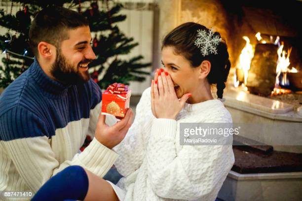 Couple near fireplace in Christmas decorated house interior. Man surprise his girlfriend for Christmas