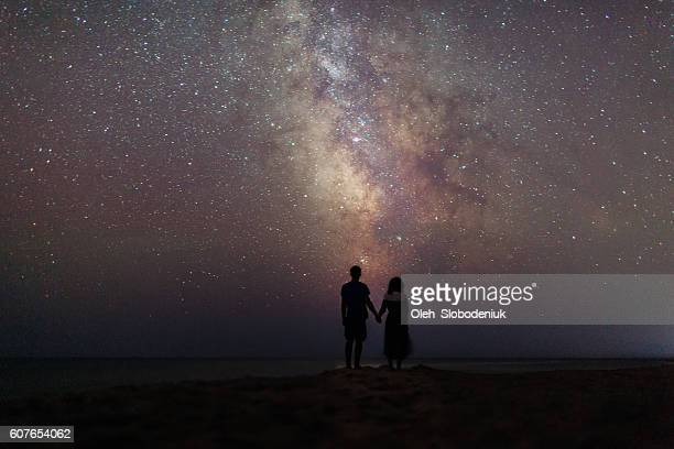 couple near the sea under the starry sky - liefde stockfoto's en -beelden