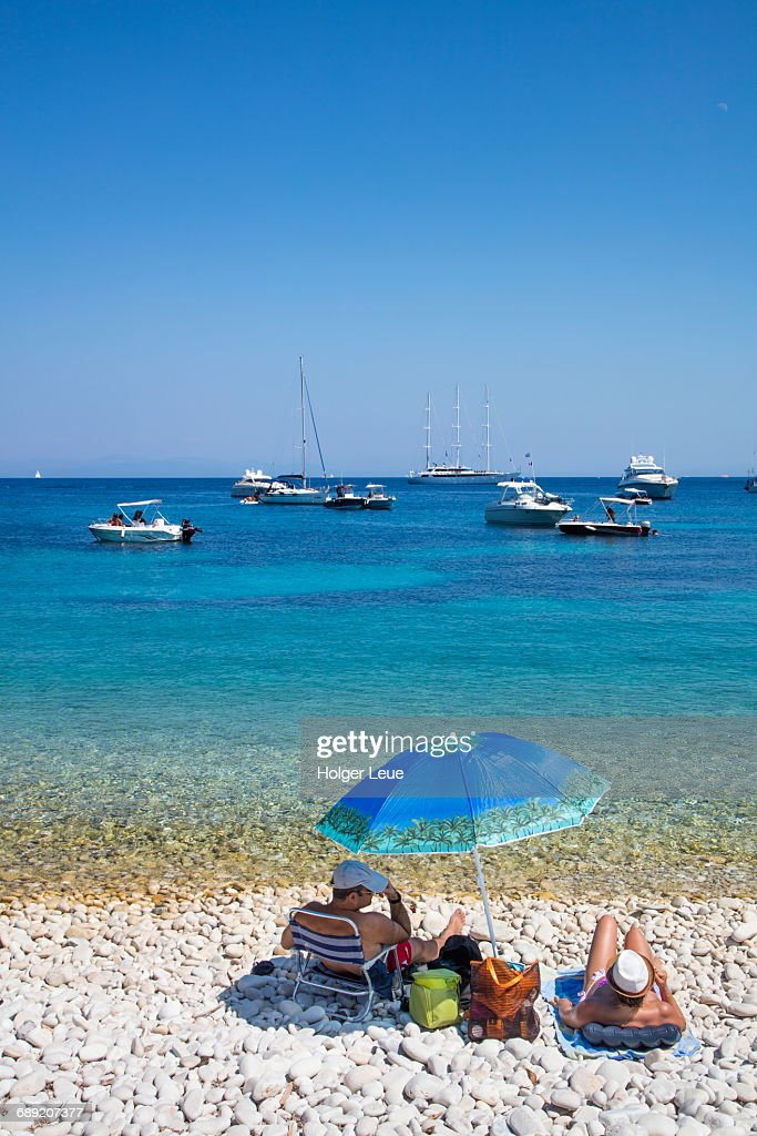 Couple next to sun umbrella on beach and sailboats : Stock Photo