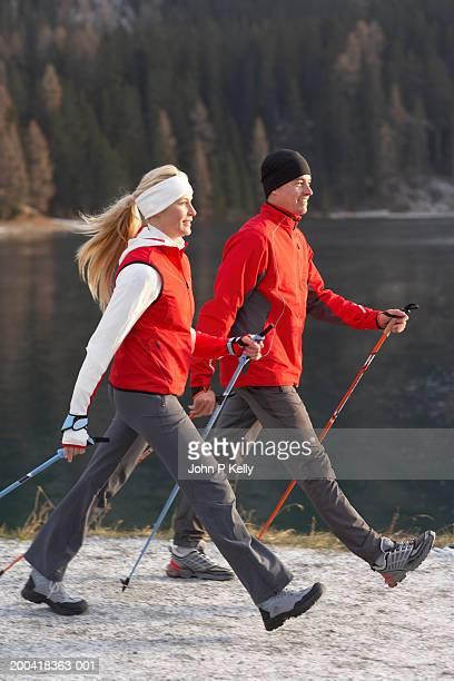 Couple Nordic walking along lakeside trail, side view