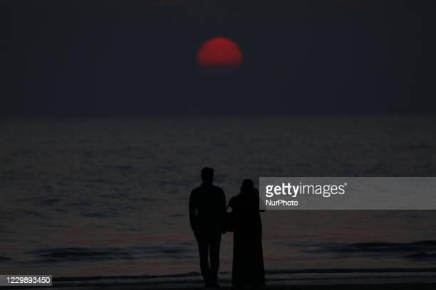 Couple observes the beauty of sunset at Kuakata sea beach in Patuakhali, Bangladesh on November 28, 2020.