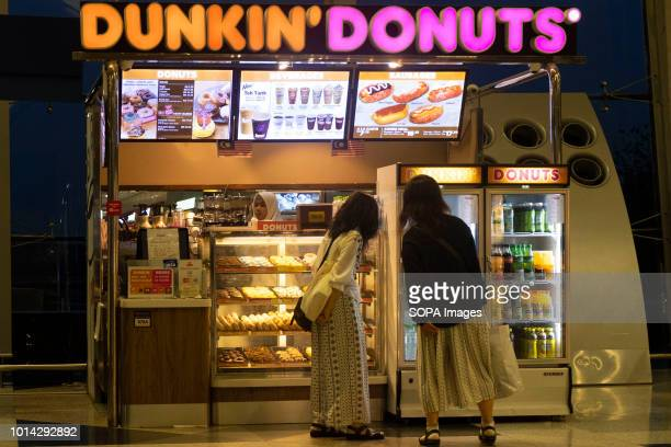 Couple of a women seen in front of the Dunkin Donuts at Kuala Lumpur International Airport also known as KLIA Malaysia Airlines Berhad airplanes seen...