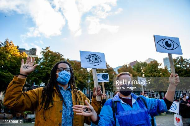 Couple of activists holding eyes drawn on placards and in their arms during the demonstration. The climate activist group, Extinction Rebellion in...
