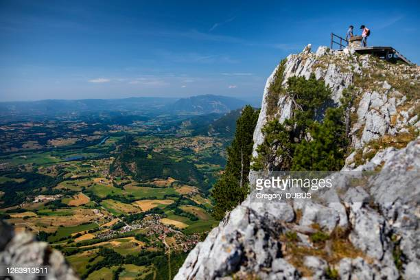 couple of adult tourists admire the view from the mountain top over the french alps landscape - grand colombier ain stock pictures, royalty-free photos & images