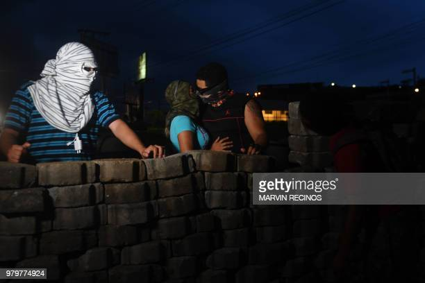 TOPSHOT A couple of antigovernment protesters kiss as they stand guard behind a barricade in Managua on June 20 2018 Nicaraguan President Daniel...