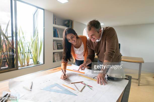 Couple of architects working at the office drawing a blueprint