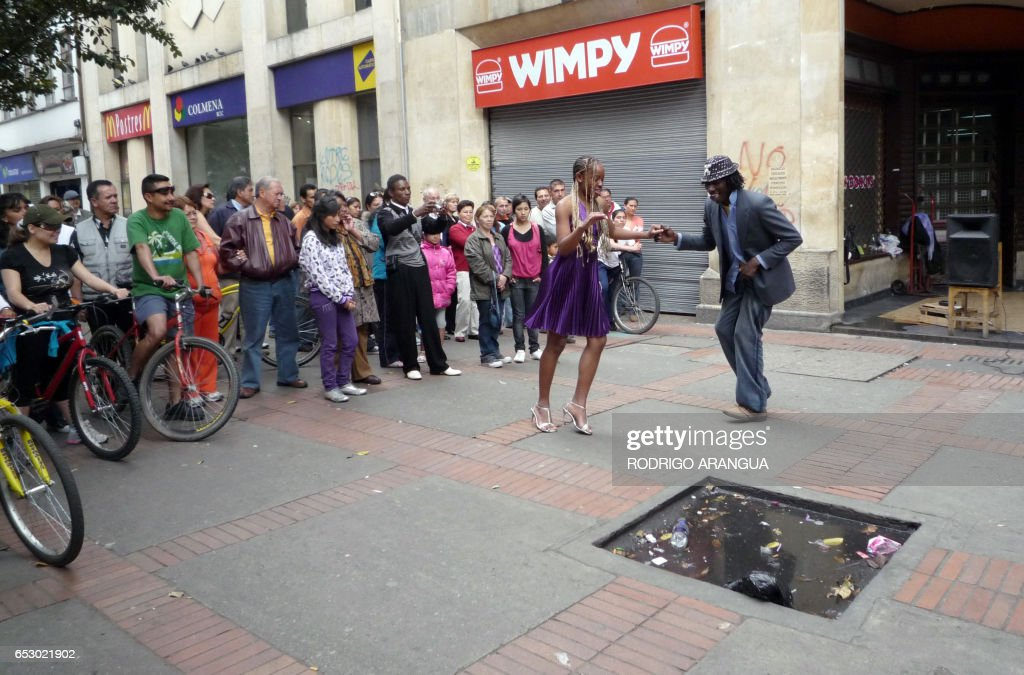 A couple of artists dance salsa along Septima (Seventh) avenue in downtown Bogota March 15, 2009. Scores of street artists entertain the public along thirteen blocks of the avenue every Friday. AFP PHOTO/Rodrigo ARANGUA /