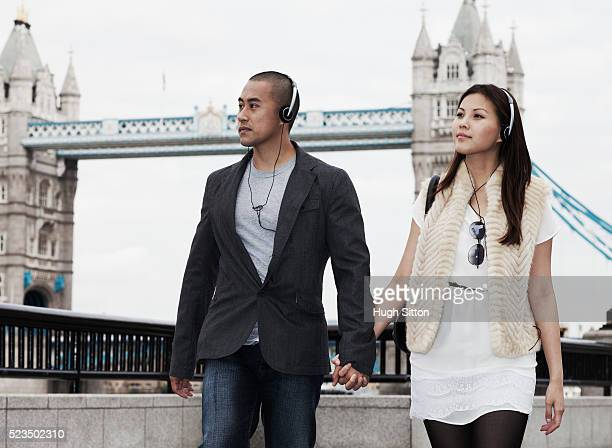 couple of asian tourists walking with tower bridge in background, london, england, uk - hugh sitton stock pictures, royalty-free photos & images