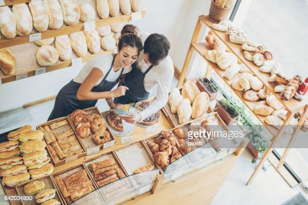 Pareja de dueños de panaderías en tableta digital