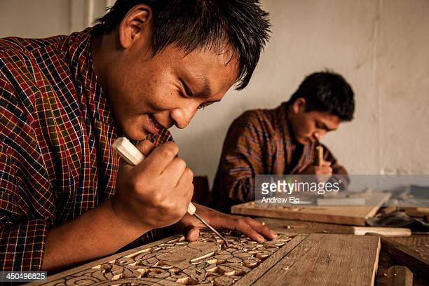 Couple of Bhutanese students learning wood carving skills at The Institute for Zorig Chusum where students undertake a six-year course on the 13...