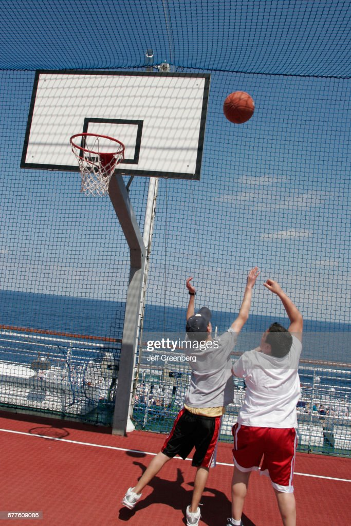 A Couple Of Boys Playing A Game Of Basketball On The Sports Deck Of