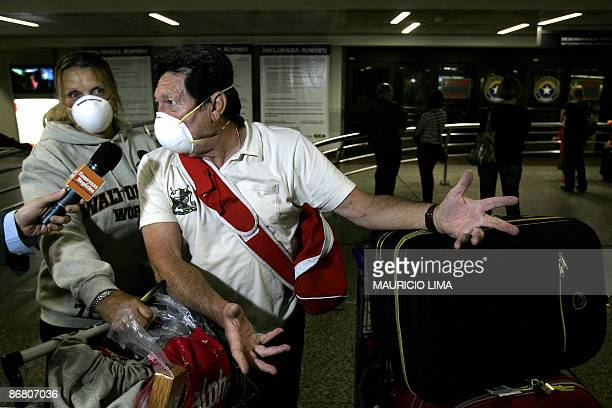 A couple of Brazilian passengers wearing surgical masks speaks with the press upon their arrival from Mexico City aboard an Aeromexico flight at...