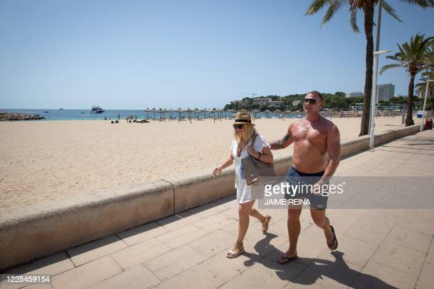 A couple of British tourists walk near Magaluf Beach in Calvia on the Spanish island of Mallorca on July 8 2020 The Balearic Islands are expecting a...