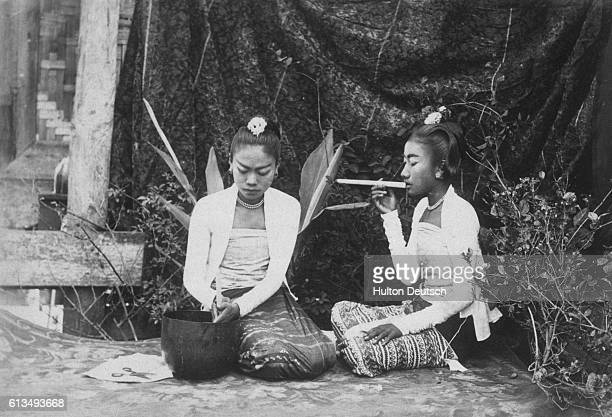 A Couple Of Burmese Young Ladies One Of Whom Is Engaged In Making Cheroots An Occupation Which Fills Up A Good Deal Of Their Time The Demand For...