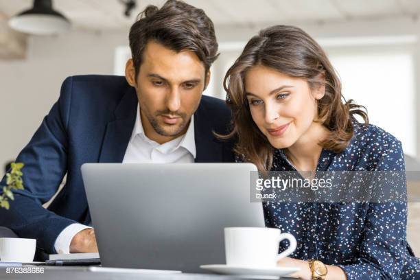 Couple of business people working on laptop at cafe