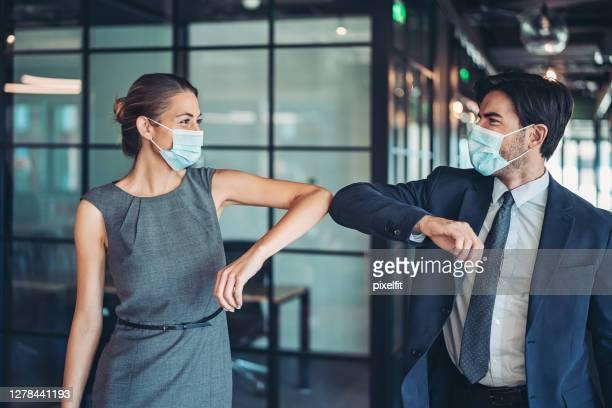casal de empresários cumprimentando com um galo de cotovelo - greeting - fotografias e filmes do acervo