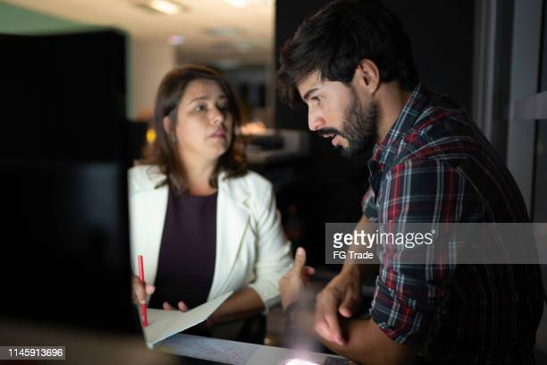 couple of business persons in the office having a discussion at night - penalty stock pictures, royalty-free photos & images