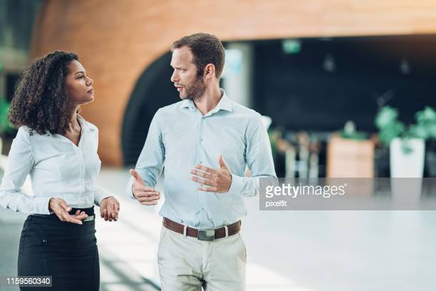 couple of business persons talking seriously in the lobby - close to stock pictures, royalty-free photos & images