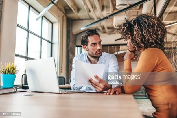 casal de pessoas de negócios falando seriamente - um do lado do outro - fotografias e filmes do acervo