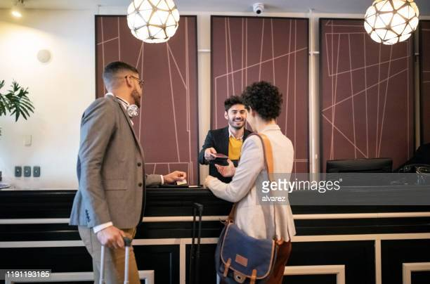 couple of business travelers checking in to a hotel - guest stock pictures, royalty-free photos & images