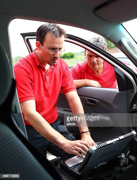 Couple of car mechanics at work.