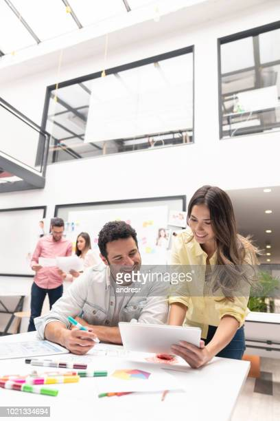 Couple of casual business people working online at a creative office