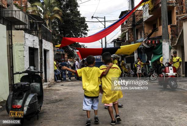TOPSHOT A couple of children wearing Colombia's national football team jersey are pictured as people watch the World Cup match between Colombia and...