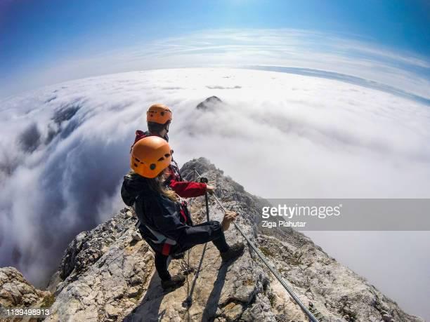 ein paar kletterer, die dem klettersteig in ein nebliges tal folgen - extremsport stock-fotos und bilder