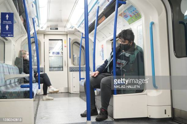 Couple of commuters wearing masks because of the Covid-19 pandemic are seen riding a London Underground tube train during the morning rush hour in...