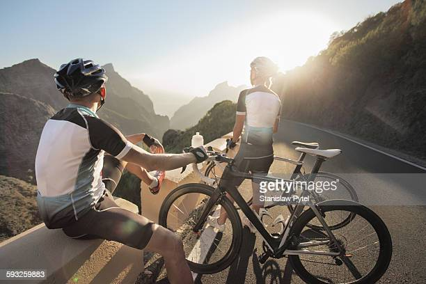 Couple of cyclists enjoying sunset in mountains