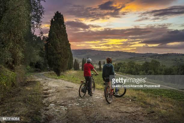 "couple of cyclists resting to admire sunset at ""villa al poggio"" on the road to san gimignano - サンジミニャーノ ストックフォトと画像"
