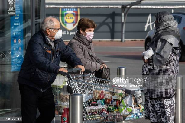 Couple of elderly people wearing respiratory masks push a trolley loaded with foodstuffs after having been given a 10-minutes access to shop in a...