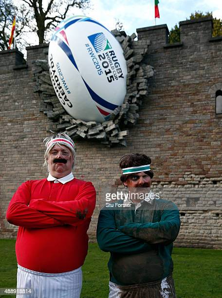 A couple of entertainers stand by a giant 2015 Rugby World Cup ball displayed on the side of Cardiff Castle on September 18 2015 in Cardiff Wales