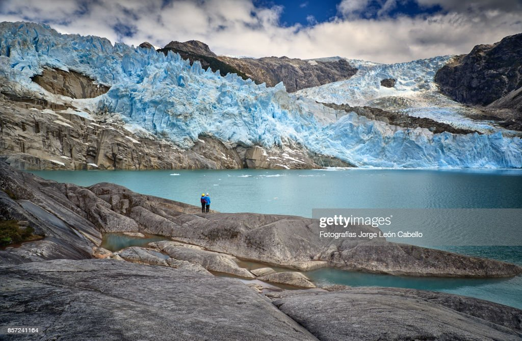 A couple of excursionist diminished by the scale of glacier Los Leones in Laguna Sn. Rafael NP : Stock Photo