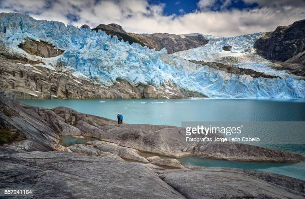 a couple of excursionist diminished by the scale of glacier los leones in laguna sn. rafael np - chile stock pictures, royalty-free photos & images