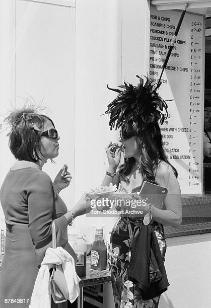 Couple of fashionable ladies tuck into fish and chips before a race at Epsom, June 2007. Epson Downs Racecourse is where the iconic Derby Festival...
