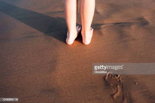 A couple of feet on the sand of the beach at sunset