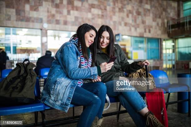 paar von freundinnen, die auf das smartphone schauen, während sie auf den zug warten - bahnreisender stock-fotos und bilder