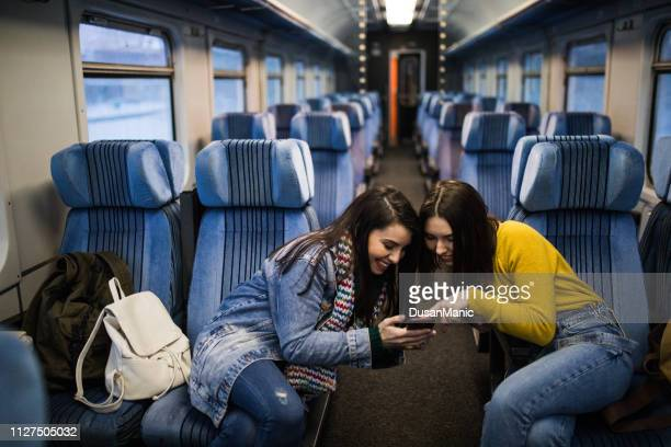 couple of female friends travel in rail car and watch on smartphone. - girlfriends films stock pictures, royalty-free photos & images