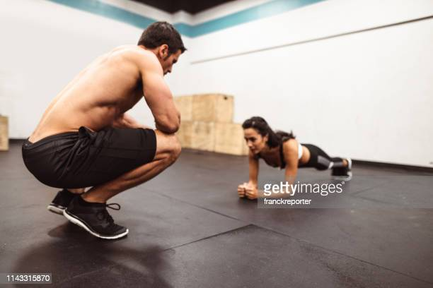 couple of fitness models on the plank position - obedience training stock pictures, royalty-free photos & images