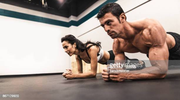 couple of fitness models on the plank position