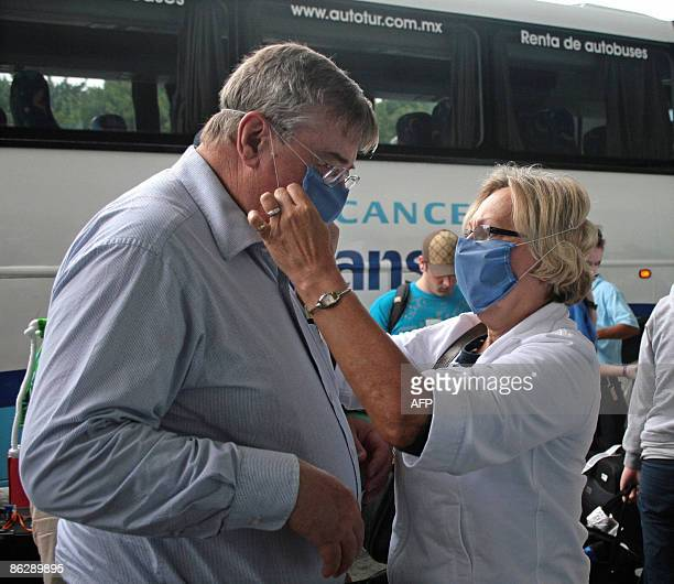 A couple of foreign tourists adjust their face masks trying to avoid contagion of the deadly swine flu virus upon arrival to Cancun airport in...