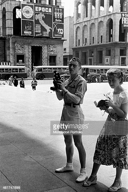 A couple of foreign tourists in Italy taking pictures and reading informations about the Duomo of Milan In the background the palazzo dell'Arengario...